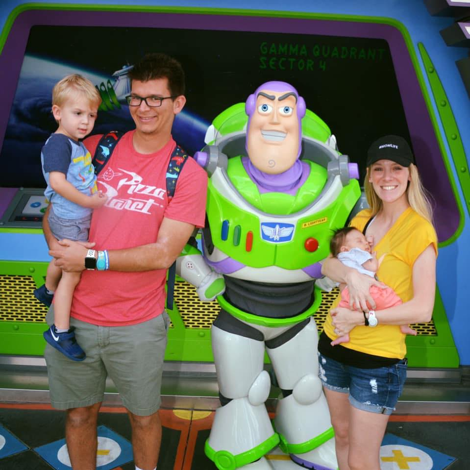Melissa and Jordan Allen holding a toddler son and baby girl taking a photo with Buzz Light-year