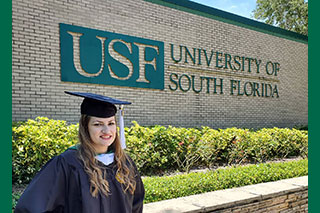 Kristen Grafton in graduate gown in front of USF University of South Florida